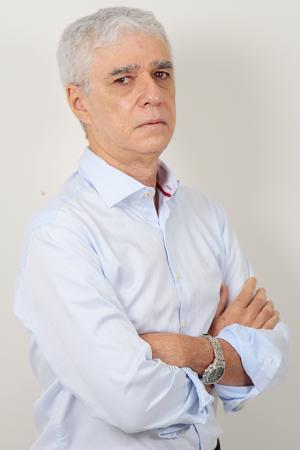 Homem de cabelo branco com blusa azul claro e braços cruzados.